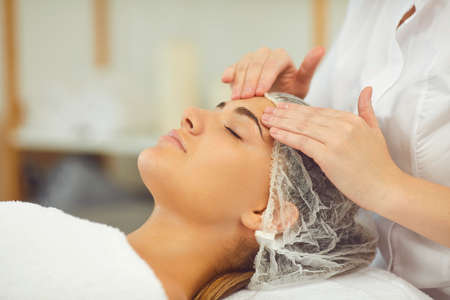 Facial massage treatment. Close-up of young woman getting procedure of relaxing facial massage treatment from cosmetologist in wellness salon, side view