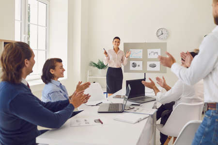 Happy company workers applauding their manager for informative and inspiring report and celebrating sales increase in corporate meeting. Coworkers clapping hands thanking young woman for presentation