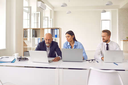 Diverse team of serious tense business people using computers, analyzing stock market data or having software problem. Group of 3 troubled company employees at desk in office working on laptops 免版税图像
