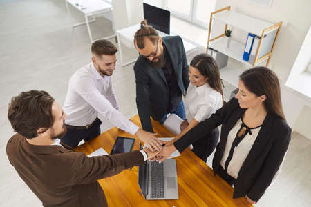 Inspired business people in office stacking hands, setting common goal, making agreement and starting new project. Professional coach motivating startup team for effective work. High angle, from above