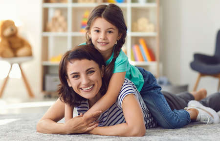 Happy mother and adorable little daughter smiling and looking at camera cuddling on rug in nursery room. Child embracing mom lying on her back. Friendly ethnic babysitter with preschool kid at home 免版税图像