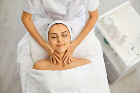 Hands of cosmetologist or masseur making massage of face, neck and upper shoulder girdle for serene young woman in beauty salon, top view. Facial treatment, skincare, cosmetology concept