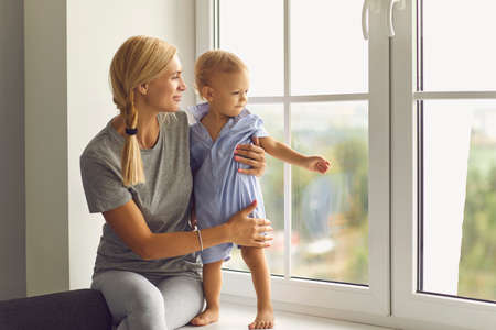 Young mother and little son looking out large new window. Happy mom and child relaxing at home. Babysitter hugging curious toddler who exploring the world and observing neighborhood from windowsill