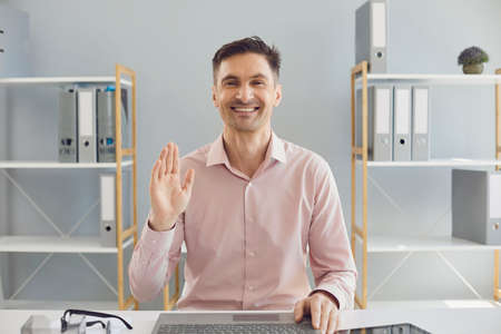 Smiling mature businessman comminucating online from home office. Positive entrepreneur waving his hand to web camera during corporate conference