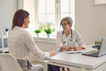 Senior confident woman doctor therapist talking and consulting young woman patient in medical clinic office during visit. Visiting doctor in hospital concept