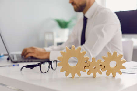 Glasses and 3 cogwheels joined together placed on office desk against blurred background of employee working on laptop. Concept of good system, implementing new ideas, effective business solutions