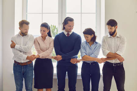 Collaboration and unity concept. Businesspeople joining effort starting new project. Team of happy coworkers engaged in corporate team building activity at work holding hands supporting each other