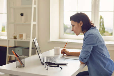 Young woman sitting at home with laptop and listening to somebody during online conversation, lesson or teleconference, side view. Online communication and elearning concept