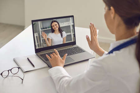 Telemedicine and online visiting doctor. Smiling young woman patient greeting her doctor online from laptop screen during videocall on laptop 免版税图像