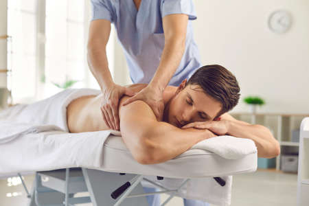 Relaxed young man enjoying medical back massage done by professional physiotherapist in modern clinic. Massagist helping male athlete reduce backache and restore energy after physical exercise 免版税图像