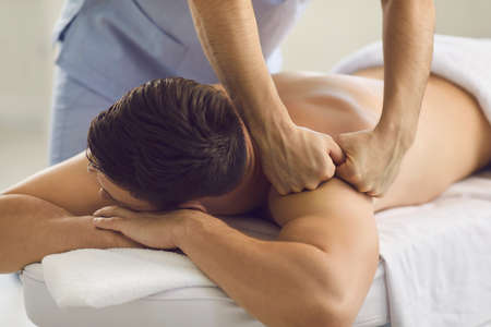 Close-up of male client getting professional body massage in spa salon or massage room. Relaxed young man lying on bed in health center enjoying remedial back massage done by qualified masseur