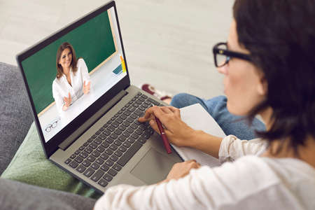 Student sitting at home, listening to online course, video conferencing and learning language. Online education. Female teacher teaching video lesson on laptop screen. 免版税图像