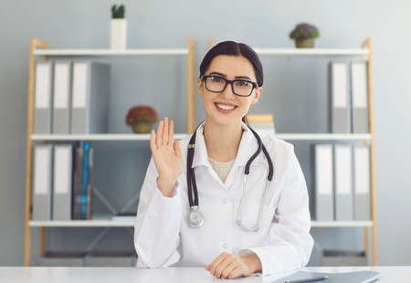 Happy female doctor waving her hand during video call with client. Therapist communicating with patient online from medical office