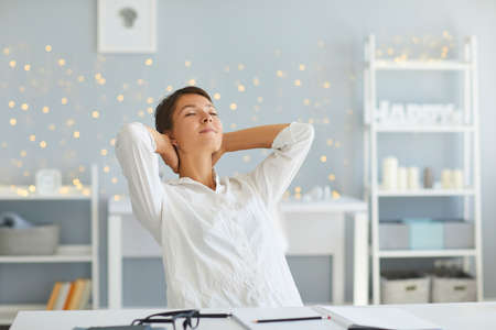 Relaxed dreamy lady sitting at desk, taking break during working day, stretching with hands behind head and eyes closed. Happy satisfied woman relaxing after finishing work in home office