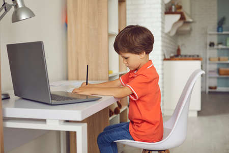 Side view of quiet concentrated child busy with homework. Serious boy sitting at desk using modern laptop computer. Little schoolchild writing in notebook while having online video lesson at home