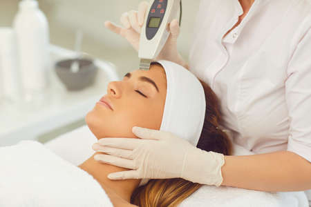 Serene woman receiving ultrasound apparatus facial cleaning from hands of professional cosmetologist in beauty salon. Professional skin cleaning concept 免版税图像