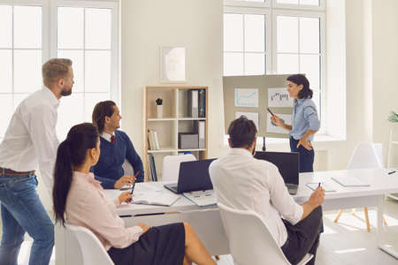 Young confident woman demonstrates some new project ideas to her partners in a conference room. Business lady making suggestions to colleagues. Startup business team on meeting in modern bright office 免版税图像