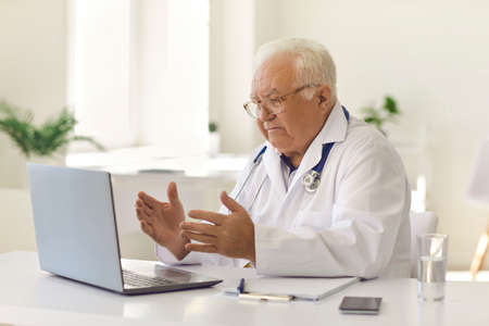 Senior male physician in white uniform with stethoscope sitting at desk in hospital office using laptop computer for video call with patient. Serious mature doctor communicating with client online Foto de archivo