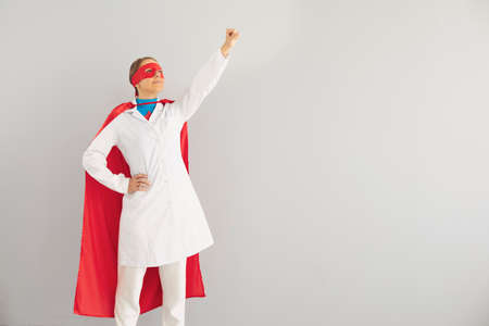 Young female doctor in superhero costume ready to fight diseases on grey background. Medical worker against infectious illnesses concept