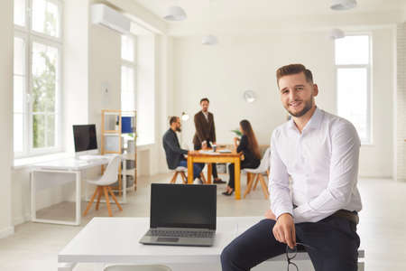 Young man with laptop with blank black screen. Business company employee with computer presenting new software product sitting on desk in coworking space and looking at camera Banque d'images