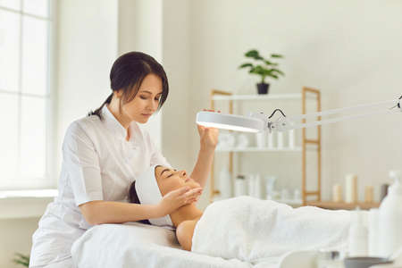 Young smiling dermatologist looking at young womans face during skin examination under lamp in beauty salon. Professional skin checking concept