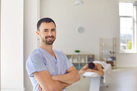 Portrait of smiling young professional masseur or physiotherapist looking at camera standing arms folded against blurred background of massage room in modern health center