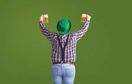 Happy St. Patricks Day. Back view a fat man in a green hat holds his hands up glasses with beer on a green background.