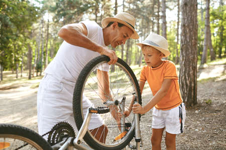 Father and son repair a bicycle in the park. Parenting.