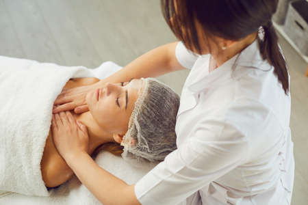 Woman masseur making professional manual relaxing massage for womans face and upper shoulder girdle in beauty spa salon, top view. Rejuvenating massage in cosmetology