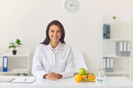 Happy smiling dietician sitting at office desk with fresh fruit looking at camera, having individual consultation with client or recording vlog or webinar about weight loss and healthy eating habits