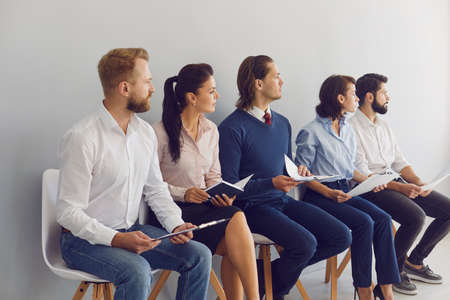 Recruitment Selection Process. Group of male and female candidates for vacancy in modern business company waiting for job interview. Young applicants with CVs sitting in queue on chairs