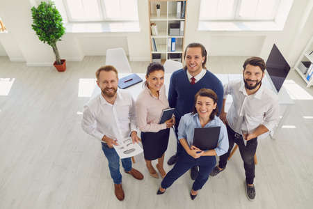 High angle of group of happy smiling Sales Department workers standing in company office looking at camera. From above Financial Planning and Analysis Team in work meeting satisfied with good result
