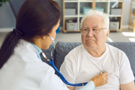 Female doctor visiting elder patient at home and checking mans heart listening to his heartbeat through stethoscope. Health screening, senior wellness check and keeping cardiovascular diseases at bay