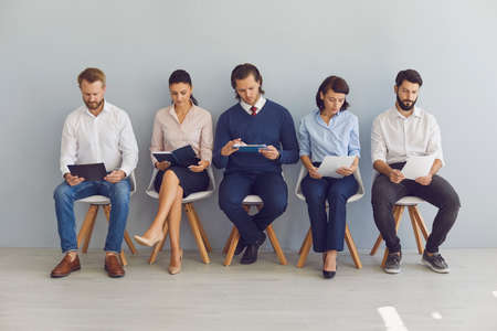 Office career seekers. Group of candidates for vacancy in modern company sitting in row preparing for interview. Young job applicants going over their resumes waiting in line for their turn