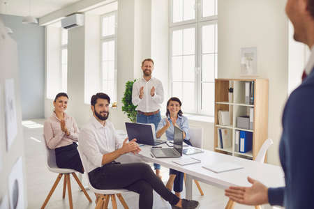 Team of happy office employees clapping hands thanking successful coworker for good presentation in corporate meeting. Grateful entrepreneurs applauding business mentor for useful advice Reklamní fotografie