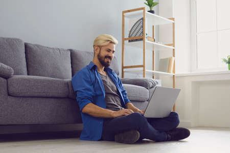 Young smiling man sitting on floor at home with laptop and working online in comfortable home conditions. Freelance, distant working and online communication concept