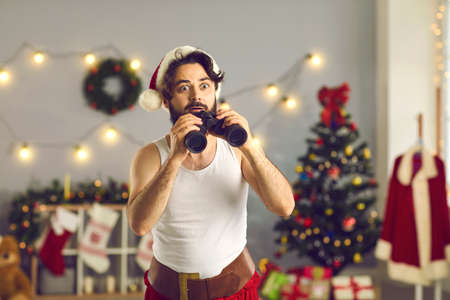 Surprised funny man holding binoculars looking out for best Christmas deals and sales, bargains, huge discounts, special offers, promos, amazing gifts and presents. Santa spy checking whos naughty