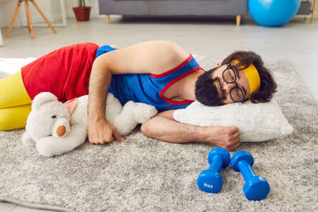 Happy, funny, relaxed, lazy man in activewear who never started exercising or working out, sleeping peacefully on floor at home, hugging a teddy bear, with dumbbells beside. Lack of motivation concept