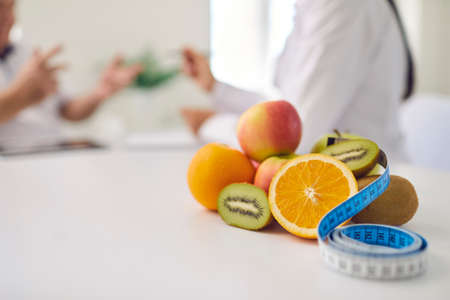 Close-up of pile of fresh apples, kiwis and oranges and measuring tape on office desk against blurred dietitian talking to patient, giving healthy diet consultation and weight loss advice Stock Photo