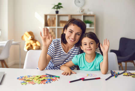 Smiling mom with little preschooler daughter greeting relatives over video call sitting at table in front of webcam. Woman and girl waving hand conveying congratulations.