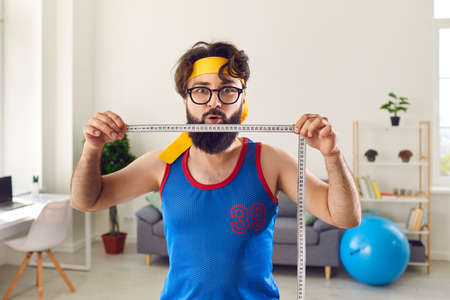 Portrait of funny young man demonstrating amazing weight loss result after regular sport workouts. Fitness instructor holding measuring tape motivating you to exercise and lose weight quickly 版權商用圖片