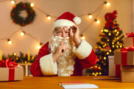 Dont tell anyone. Santa Claus or Father Christmas in red and white suit and spectacles looking at camera and saying Shush asking you to keep silent as hes going to share a wonderful, magical secret