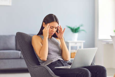 Tired young Asian woman massaging temples suffering from headache or migraine after working on laptop computer sitting in armchair in home office. Concepts of health problems, stress and overworking