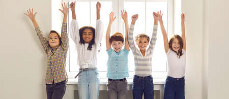 Header with group of happy smiling diverse children looking at camera standing backlit by the window with arms raised. Fun, success, celebrating victory, confidence in future and dreaming big concepts Banco de Imagens