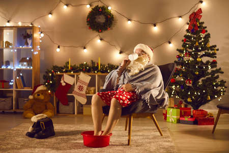 Tired Father Christmas or Santa Claus relaxing in comfy armchair at home, enjoying cup of hot tea and soaking his cold feet in warm water after long day of work
