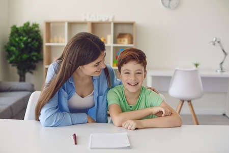 Smiling little red-haired boy is about to write down a task on a piece of paper with the help of his mother sitting at a table in the room. Learning assistance concept.