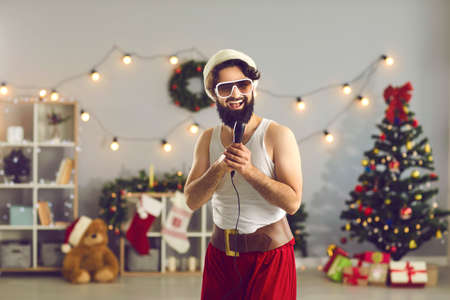 Cheerful man in Santa cap and funny holiday costume standing and singing in microphone over decorated home with Christmas tree at background. Christmas and New Year at home concept