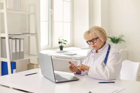 Mature woman doctor in uniform and glasses consulting patient online on laptop during videocall or online meeting in clinic office. Telemedicine and online medicare concept Foto de archivo