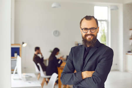 Portrait of happy smiling bearded company CEO in glasses looking at camera. Intelligent young businessman, confident startup founder, charismatic team leader standing arms folded in office. Copy space