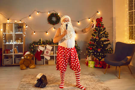 Funny grandpa in undershirt, Santa Claus beard, hat and striped socks holding mike and singing Christmas songs at karaoke night party at home. Senior man having fun and relaxing on New Year holidays Stock Photo